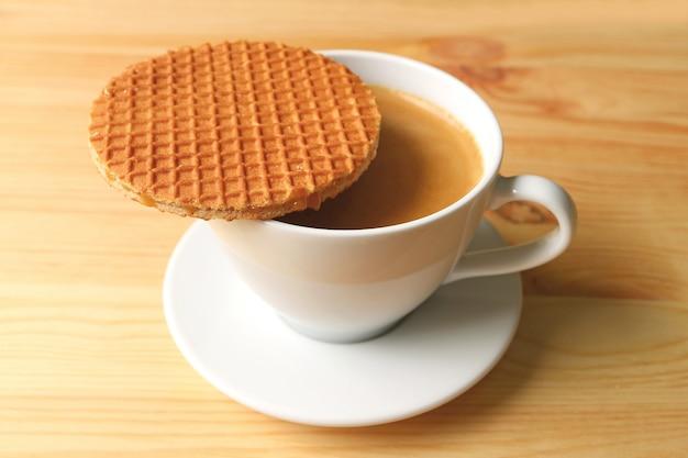 木製のテーブルで提供されるホットコーヒーのカップの上に置かれたストロープワフェル