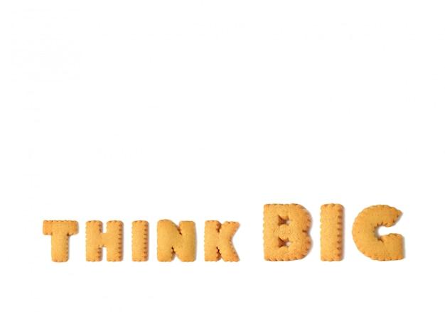 白い背景に分離されたアルファベットの形をしたクッキーで綴られた単語を考える