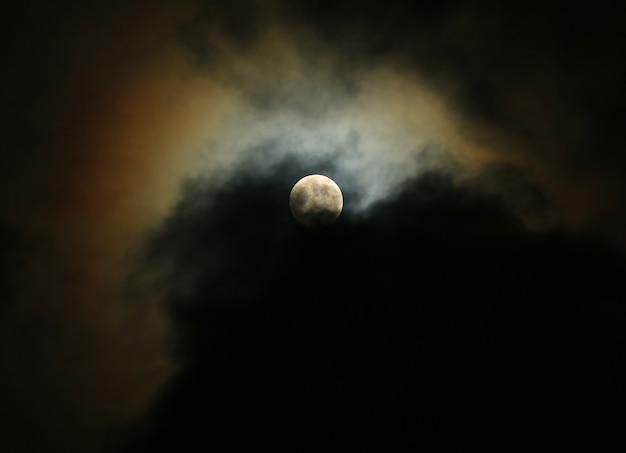 雲に映る月光と夜の曇り空に月