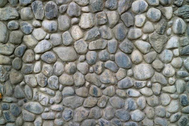 灰色の丸い石の壁のテクスチャ背景