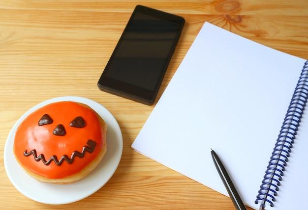 Пончик джека о фонаря хэллоуина со смартфоном и записной книжкой вяжущего кольца на деревянном столе