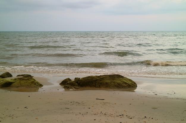 曇りの夜に海の波と熱帯のビーチ