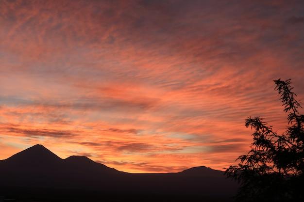 チリ、サンペドロデアタカマの山脈のシルエットの見事な色のグラデーション