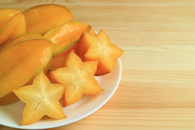 オレンジ黄色の全体の果物と木製のテーブルにスライスしたスターフルーツ