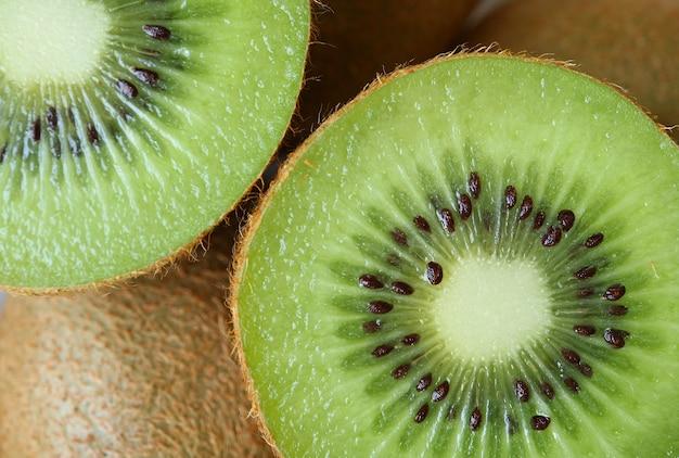 半分活気のある緑の新鮮でジューシーな熟したキウイフルーツのカットの質感で引けた