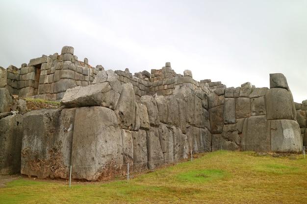 サクサイワマンインカの歴史的な要塞、クスコ、ペルーの太陽の門(道標に書かれたインティプンク)