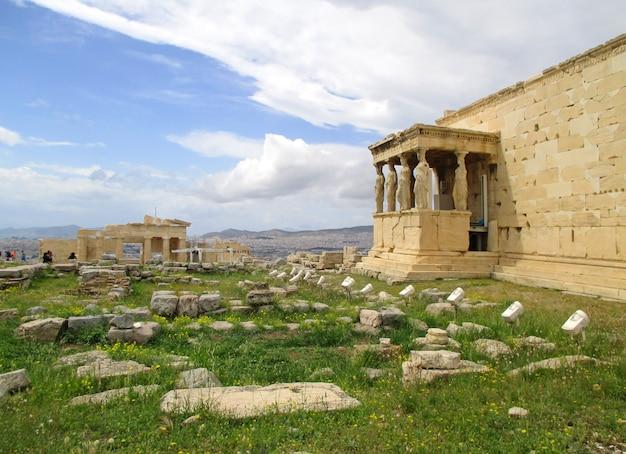 遠くにプロピュライア記念碑の門があるエレクテイオン古代ギリシャ神殿のポーチのカリアティード柱