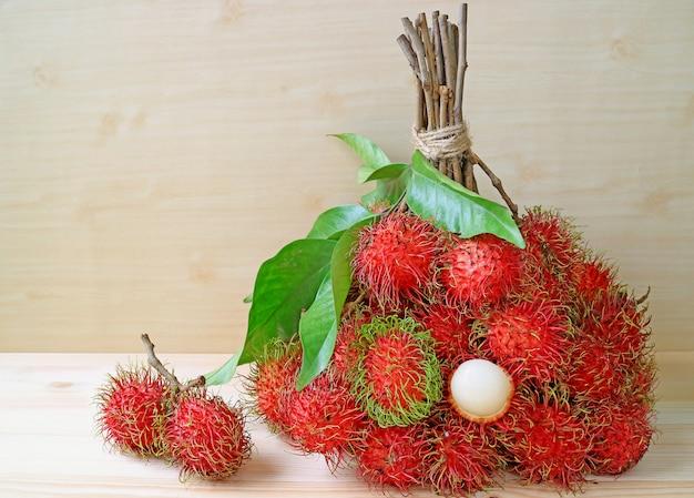 Букет из ярких цветных красных и зеленых свежих спелых рамбутана цельных фруктов на деревянный стол