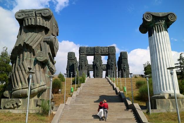 ジョージアの国のトビリシ市の近くの丘の上にある顎を落とす記念碑であるジョージアのクロニクルの階段をカップルします