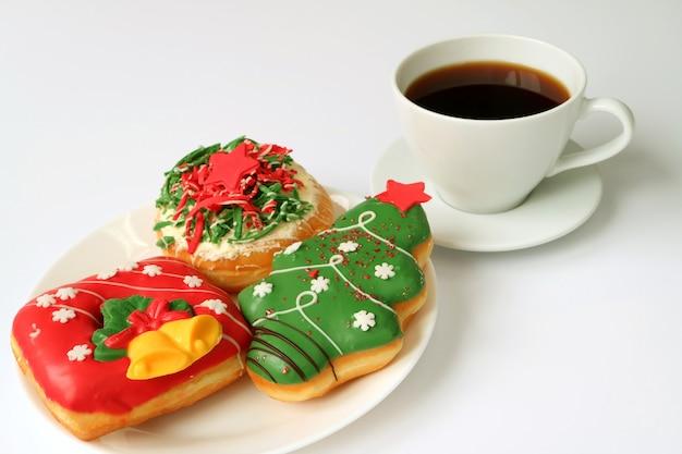 一杯のコーヒーと白いプレートにクリスマスのお菓子のプレート