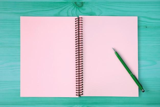 開いたノートと青緑色の木製テーブルの上の緑のペンのピンクの空白ページ