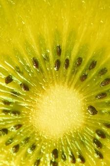 背景の鮮やかな黄色のキウイフルーツの断面の垂直方向の画像