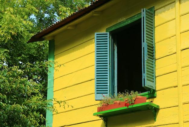 Синие деревянные ставни на ярко-желтый дом среди зеленой листвы в солнечном свете