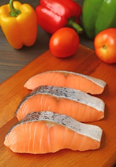 Вертикальное изображение сырых ломтиков лосося на деревянной разделочной доске со свежими овощами