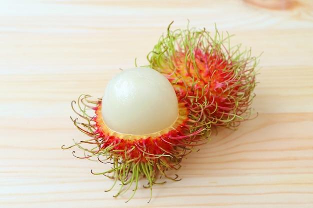 Целые фрукты свежего спелого рамбутана и очищенные от кожуры, чтобы показать свою белую сочную мякоть на деревянном столе