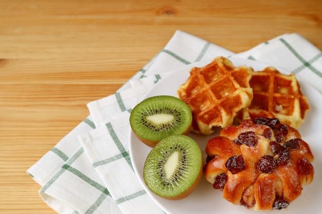 ベルギーワッフルとクランベリーパン、白いプレートにカットキウイフルーツを木製のテーブルで提供しています