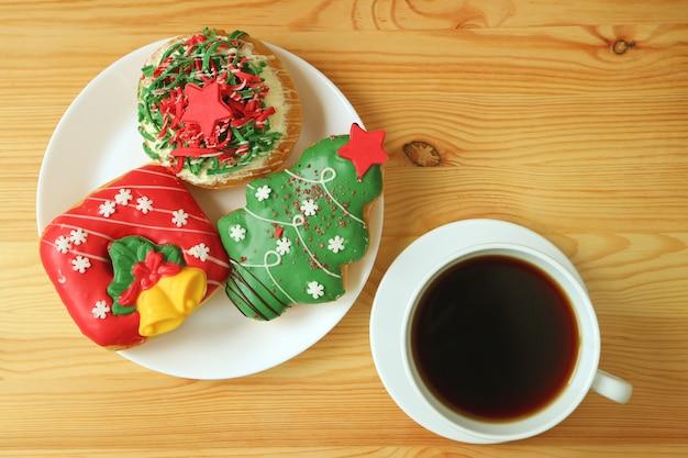Вид сверху чашку горячего кофе и тарелку украшенные рождественские сладости на деревянный стол