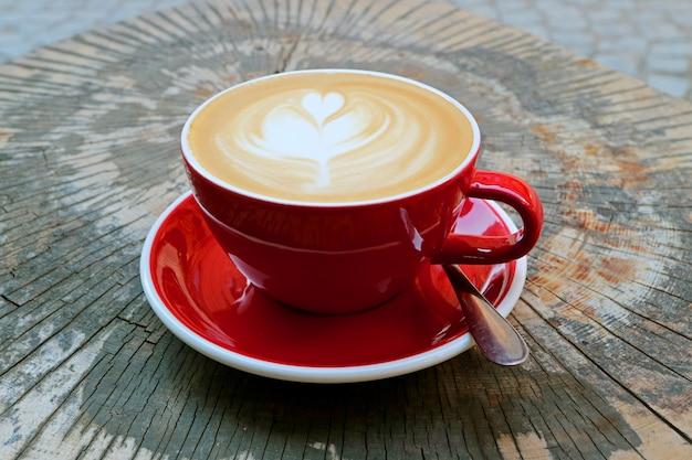 木の切り株のテーブルで提供しています赤いカップで熱いカプチーノコーヒー