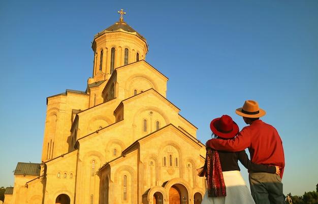 トビリシ、ジョージア州の聖三位一体大聖堂に感銘を受けているカップル