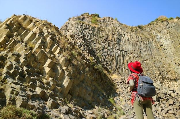 アルメニアのガルニ渓谷に沿った玄武岩の列の形成の信じられないほどの交響曲に感銘を受けた女性
