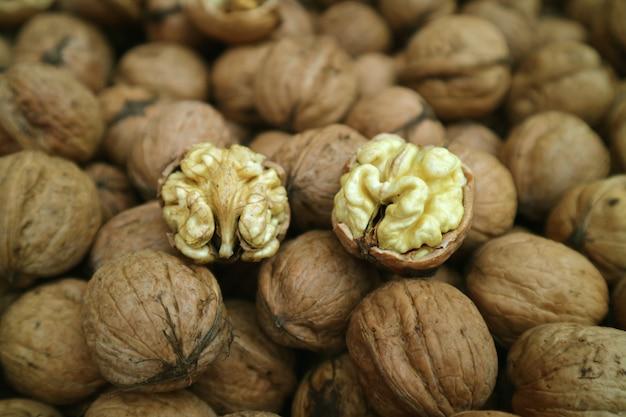 Крупным планом ядра сырого грецкого ореха на куче грецких орехов с орехами
