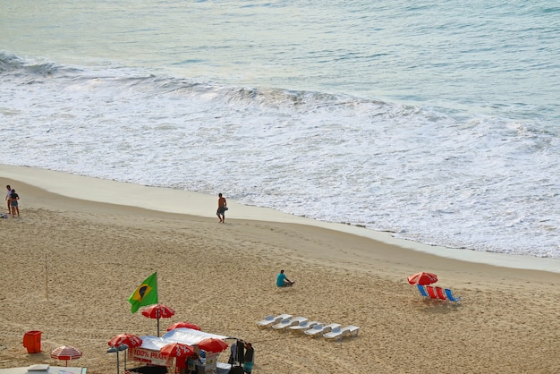 Красочные шезлонги и зонтики на волнистом пляже копакабана, рио-де-жанейро, бразилия