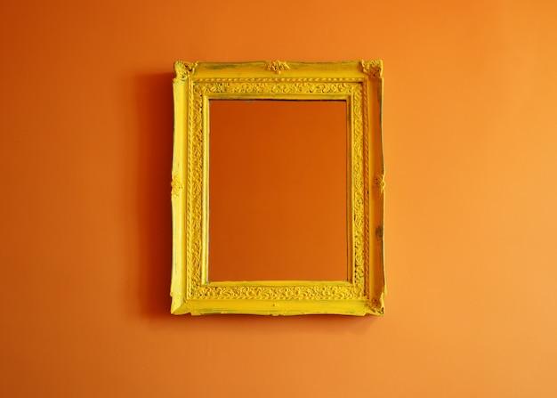 Желтая античная пустая рамка для фотографий на оранжевом фоне стены