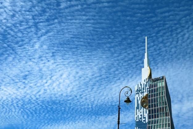 Современный небоскреб и уличный фонарь на фоне солнечно-голубого неба с облаками из кучевых облаков, батуми, грузия