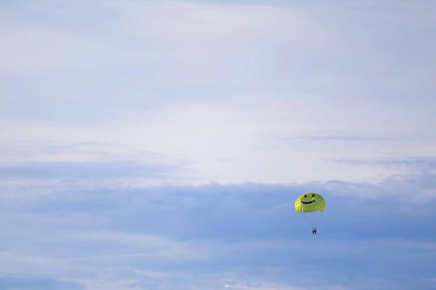 水色の空を飛んでいる黄色の幸せそうな顔のパラシュート