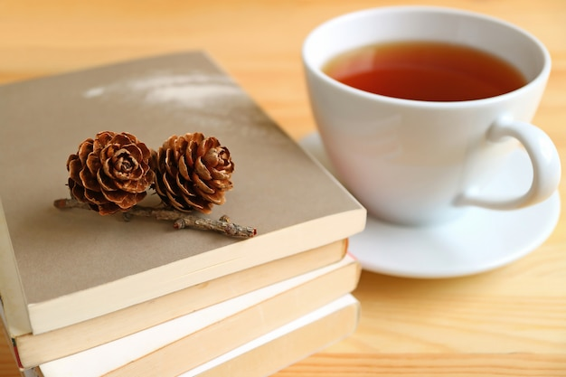 熱いお茶のカップの背景をぼかした写真と書籍のスタック上のローズパインコーン