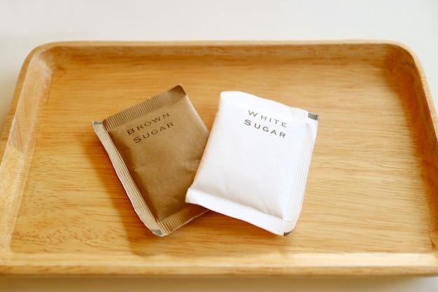 木製トレイに分離されたブラウンシュガーと白砂糖の袋