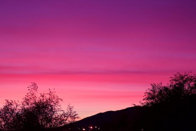 丘と夢のような紫色の空と木のシルエット