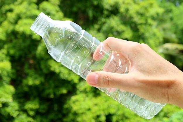 Рука пустую пластиковую бутылку питьевой воды с зеленой листвой на заднем плане