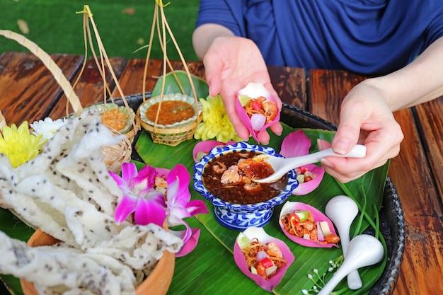 Женская рука держит свежую закуску в виде лепестка лотоса, выкапывая пряный соус