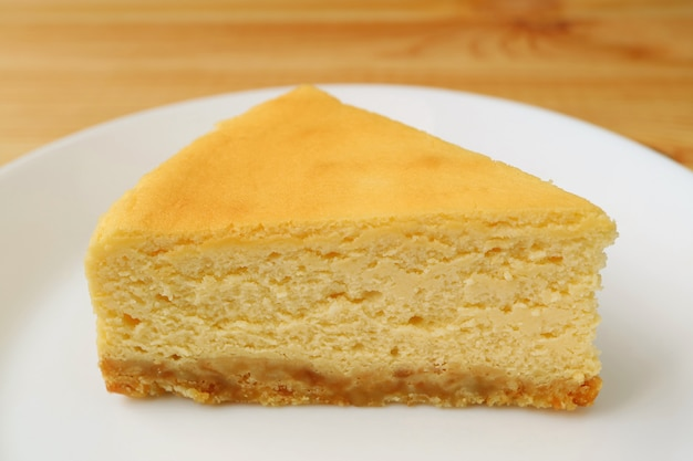 白い皿に自家製のクリーミーな黄色のプレーン焼きチーズケーキのスライス