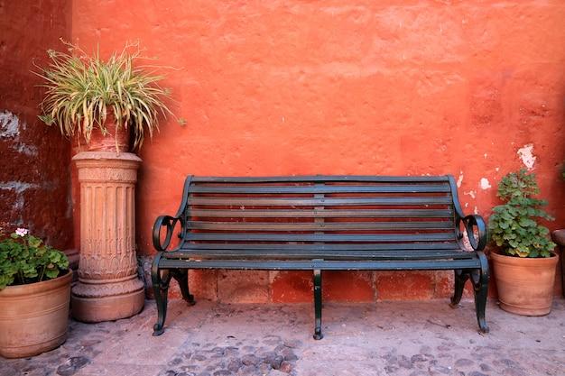 Черная деревянная скамья перед шероховатой стеной оранжевого цвета с множеством терракотовых плантаторов, перу