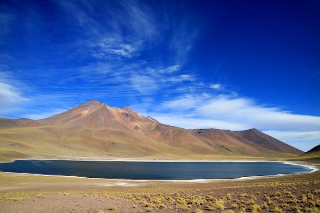 Озеро лагуна миникес или миникес с вулканом серро мисканти в высокогорье на севере чили