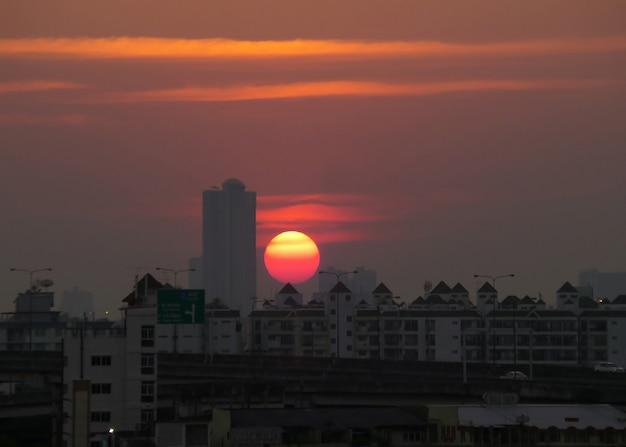 活気に満ちた色の夕日はバンコクの都市、タイの建物の上
