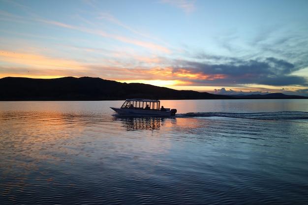 日没、プーノ、ペルーでチチカカ湖のクルージングボートのシルエット