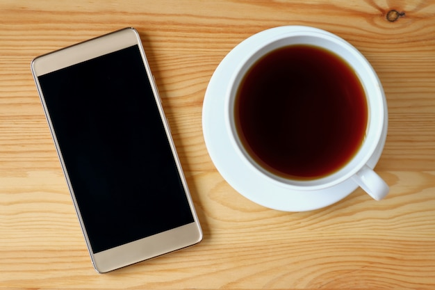 Вид сверху золотой смартфон с чашкой горячего чая на деревянный стол