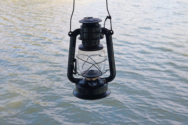 湖のさざ波に対するレトロな石油ランプ
