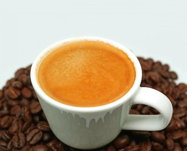 デザインやテキストのための空き領域を持つ焙煎コーヒー豆の山の上のホットエスプレッソコーヒー