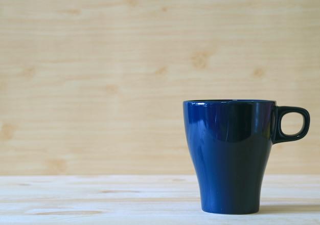 Вид спереди кружка темно-синего цвета на деревянный стол светлого цвета