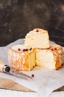ドイツ製またはフランス製のソフトチーズ、オレンジ色の皮をむいたスライス、ワックスペーパー、フォーク