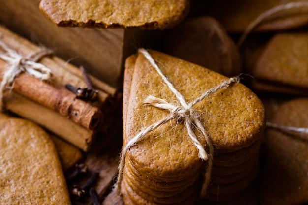 クリスマスジンジャーブレッドの菓子クッキーのスタックは、絡み合いで結ばれています。シナモンはクローブをつくる。