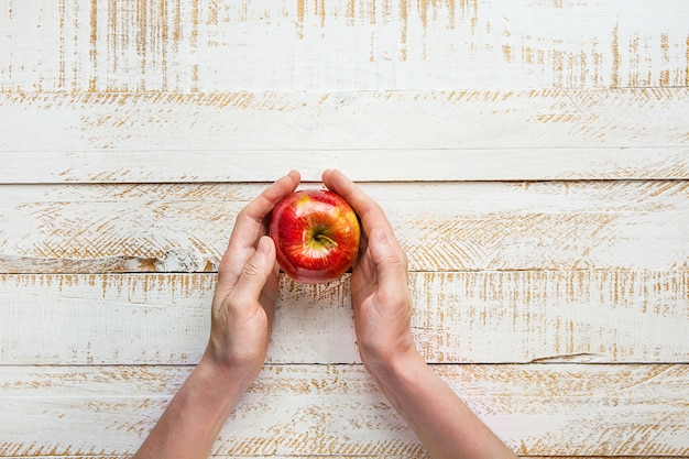Руки молодой женщины держа зрелое красное яблоко на белой таблице древесины планки. благодарение