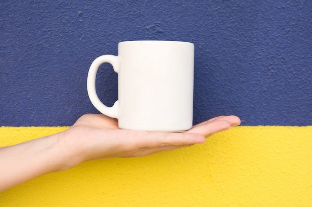 若い白人女性を手に保持します。ダブルトーンダークブルーイエロー塗装壁に手のひら空白モックアップホワイトマグカップ