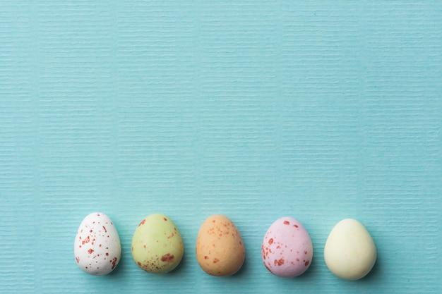 水色のターコイズブルーの背景に色とりどりの斑点チョコレートイースターエッグの行