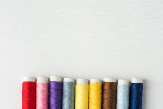 Ряд разноцветных швейных ниток на картонных катушках. белый деревянный фон.