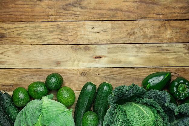 板ウッドの背景の下のボーダーに配置された緑の野菜の品揃え。